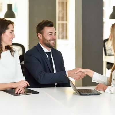 Smiling young couple shaking hands with an insurance agent or investment adviser. Three people meeting in an office reaching an agreement